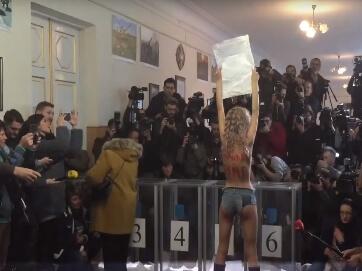 """""""Сутенера до в'язниці!"""" - Фемен пікетували голосування Кличко. Традиційно дівчата привертали увагу до акції голими грудьми. Оголену активістку вивели з дільниці охоронці."""